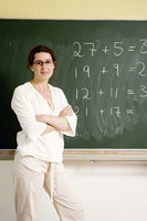 Woman standing in front of the blackboard with her arms folded