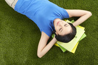 Woman studying while laying on the grass