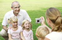 Woman taking pictures of her husband and daughters