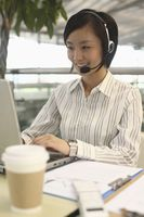 Woman talking on telephone headset while using laptop