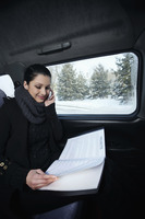 Woman talking on the phone and reading document while traveling in the car