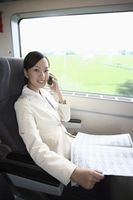 Woman talking on the phone and reading newspaper while traveling on the train
