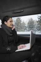 Woman talking on the phone and using laptop while traveling in the car