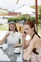 Woman talking on the phone while her friend is enjoying coffee