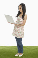 Woman using a laptop while standing
