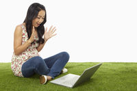 Woman using laptop and looking surprised