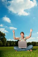 Woman using laptop in the park, arms raised