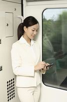 Woman using pda phone while traveling in train