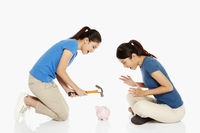 Woman wanting to hit the piggy bank with a hammer