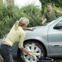 Woman washing car wheel, man washing windshield with squeegee