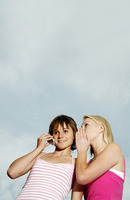 Woman whispering to her friend who is talking on the mobile phone