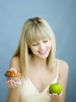 Woman with a cupcake and green apple
