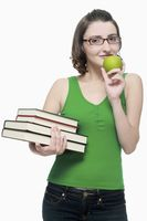 Woman with a stack of books and a green apple