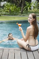 Woman with glass of cocktail sitting by the pool side, man swimming towards woman
