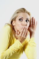 Woman with hand covering mouth while eavesdropping