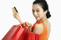 Woman with shopping bags holding up credit card