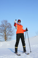 Woman with skis and poles showing thumbs up