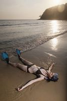 Woman with snorkeling gear lying on the beach