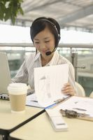 Woman with telephone headset reading report