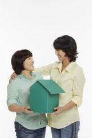 Women holding a cardboard house