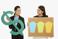 Women holding up a dollar sign and a pin board