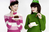Women with party hats enjoying cakes