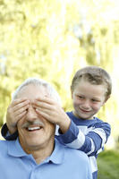Young boy covering his grandfather's eyes