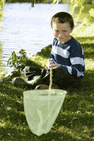 Young boy sitting by the lake side holding fishing net