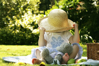 Young girl playing with hat while picnicking in the park