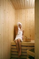 Young woman in sauna, wiping sweat