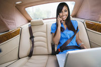 Young woman talking on phone in car