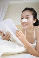 Young woman with nose strip lying forward on the bed reading book