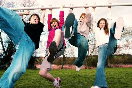 Girl : A group of kids hanging onto the goal post kicking