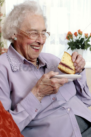 Food : An old bespectacled woman sitting on the couch eating cake