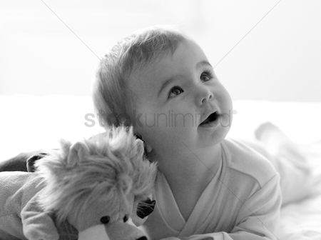Cute : Baby girl lying forward on the bed with her toys