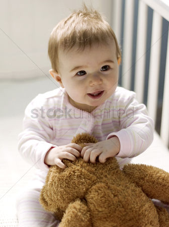 Girl : Baby girl playing with her teddy bear in the crib