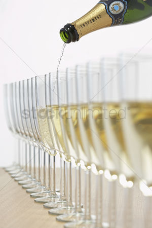 Wedding : Bottle of champagne filling row of glasses selective focus