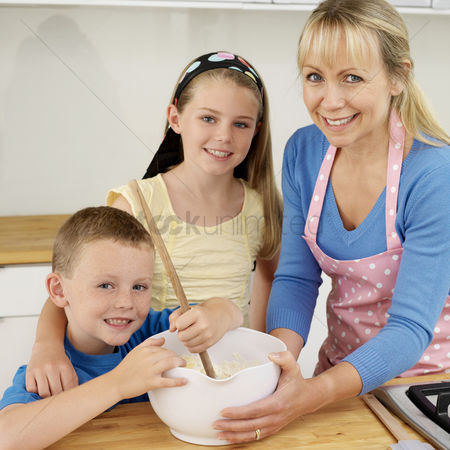Girl : Boy using wooden ladle  woman and girl smiling at camera