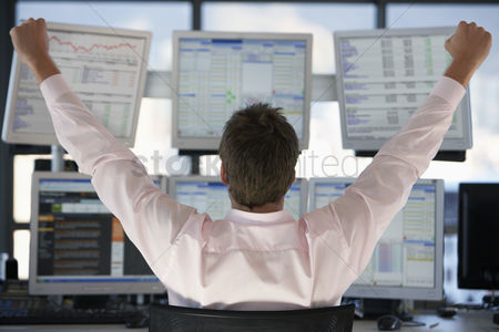 Interior : Businessman watching computer screens with arms raised back view
