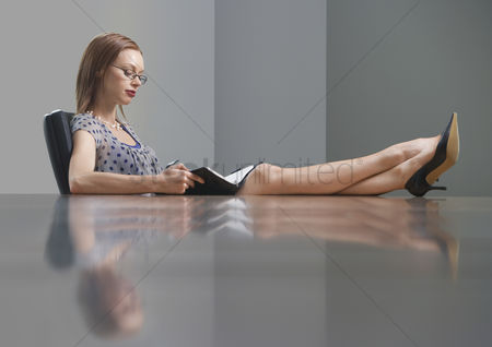 Interior : Businesswoman sitting and studying book feet on table side view