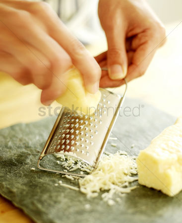 Food : Chef grating parmesan cheese onto a slate surface