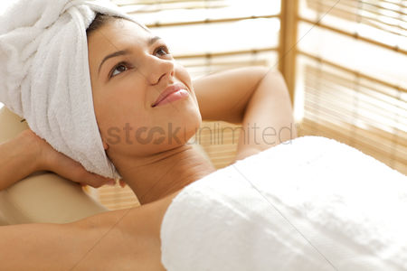 Spa : Close-up of young woman relaxing on massage table with hands behind head