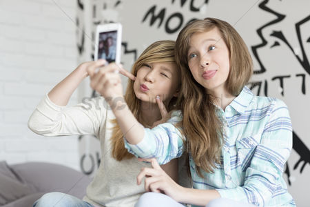 Girl : Cute sisters pouting while taking photos with smart phone at home