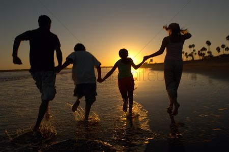 Girl : Family running through sea holding hands at sunset back view silhouette