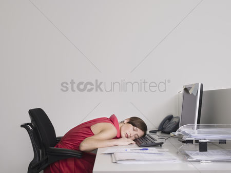 Interior : Female office worker asleep at desk in office