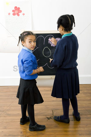School : Girls colouring a drawing on chalkboard