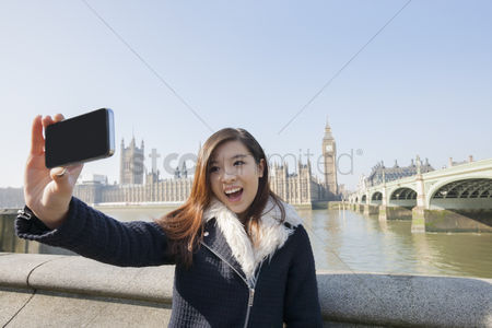 Selfie : Happy young woman taking self portrait through cell phone against big ben at london  england  uk