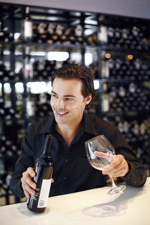 Food : Man holding a bottle of wine and a wine glass