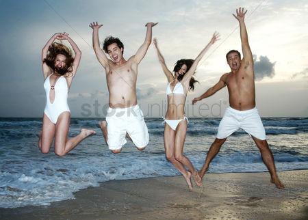 Celebration : Men and women jumping happily on the beach