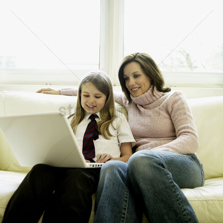 Girl : Mother and daughter sitting on the couch using laptop